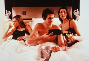 Two young women and a man in bed.